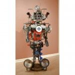 Johnnie Salvage found object assemblage by John Schwarz, a humanoid robot creature made out of headlamps, engine parts, and other scrap metal.